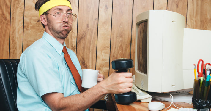 A man and office in 1980's - 1990's style, complete with vintage computer and technology of the time, lifts some small hand weights, getting a short exercise break while remaining at his desk.  He wears a sweatband on his head, taking a short breather from his weight training and drinking some coffee.  Wood paneling on the wall in the background.  Horizontal image.