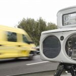 A yellow van drives very fast past a speed camera - threatens here the digital speeding ticket