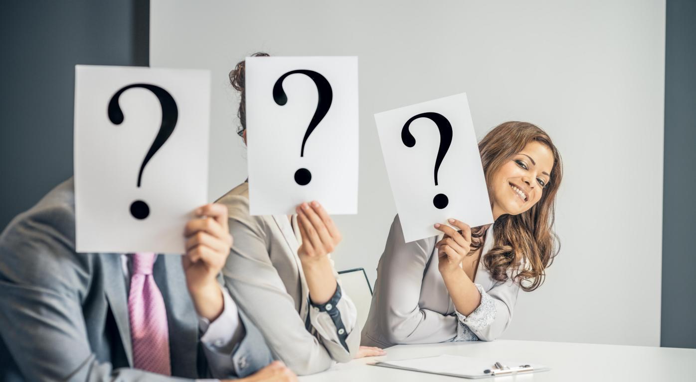 Drei Business-Leute halten Fragezeichen vor Ihr Gesicht: Wer ist der Richtige im Recruiting-Prozess?
